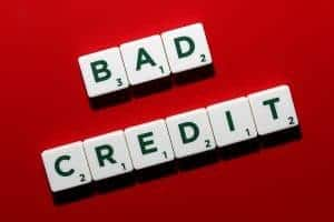 Adverse Credit Loans bad credit letters scrabble on red table