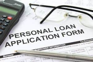 Bad Credit Personal Loan application form on desk with pen and glasses